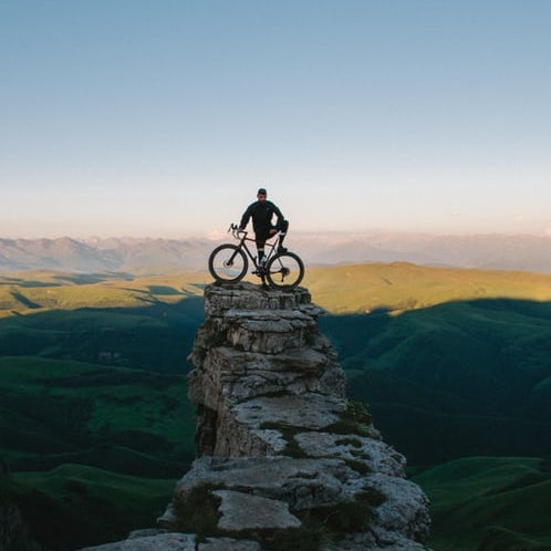 Man on rock with bike